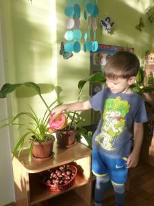 Егорка поливает цветы